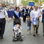Ezra Friedlander (left) walks beside Scott Stringer and family, with Leon Goldenberg (right)